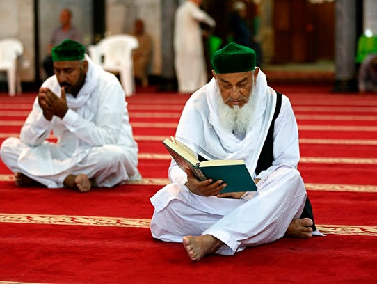 Muslim worshippers read the Quran, Islam's holy book,