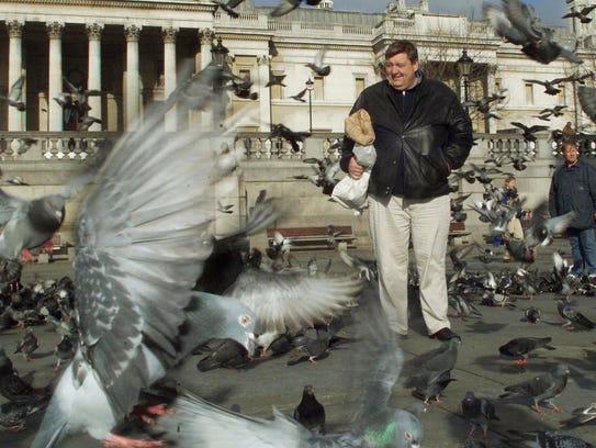 Bernard Rayner feeds the pigeons in London's Trafalgar