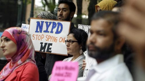 In this Aug. 28, 2014, file photo, a group of people hold signs protesting the New York Police Department's program of infiltrating and informing on Muslim communities during a rally near police headquarters in New York. On Tuesday, April 15, 2014, the NYPD confirmed it disbanded the special intelligence unit that monitored Muslim communities in New York and New Jersey.