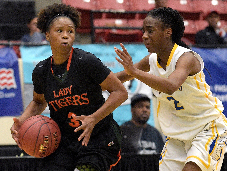Dunbar's Keri Jewett (3) drives past Cardinal Newman's Anise Williams (2) during a girls basketball game at the FHSAA State Finals, Tuesday, Feb. 17, 2015, in Lakeland, Fla.(Photo/Phelan M. Ebenhack)