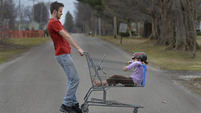 Caleb Miller, 17, spins his sister Evelyn Miller, 5, in a cart they found on a warm winter day near their home, Tuesday, Feb. 20, 2018, in Springfield Township, Pa.