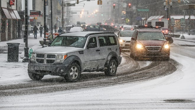 Cars make their way through Downtown streets as snow falls in Indianapolis on Friday, Dec. 29, 2017.