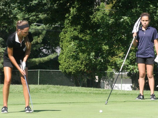 Churchill's Paige Peterson watches her putt on the