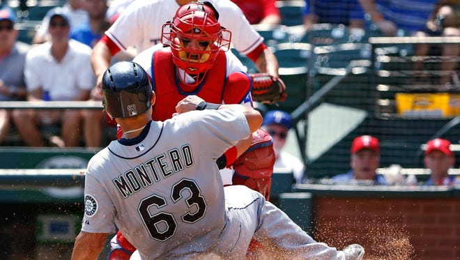 Texas Rangers catcher Bobby Wilson makes the tag at the plate on Seattle Mariners' Jesus Montero (63) for an out during the seventh inning of a baseball game Wednesday, Aug. 19, 2015, in Arlington, Texas. The Rangers defeated the Mariners 7-2.