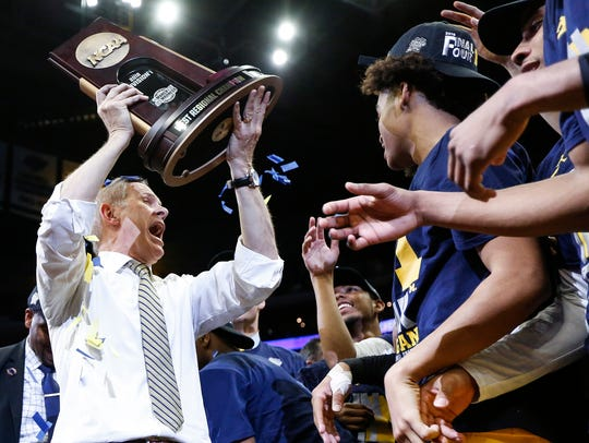Michigan coach John Beilein celebrates and raises the