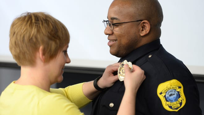 The Green Bay Police Department swore in five new officers April 6, 2015. Ptl. Aaron Walker has his shield pinned to his uniform by wife Megan following the oath.
