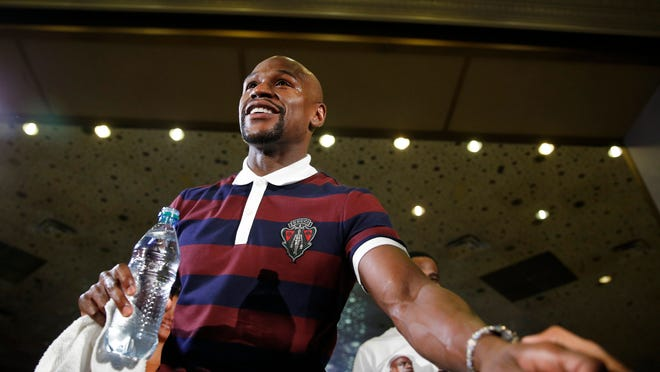 Floyd Mayweather Jr. stands on stage during the grand arrival Tuesday for his upcoming fight against Andre Berto. (Photo by John Locher, AP)