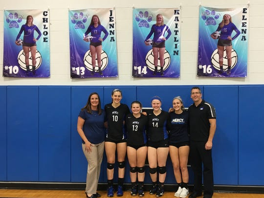 Coach Denise Harvey, Chloe Klusman, Jenna Campbell, Kaitlin Goedde, Elena Schmitt and coach Greg Samuels pose in front of the Mother of Mercy High School 2017 senior banners for volleyball.