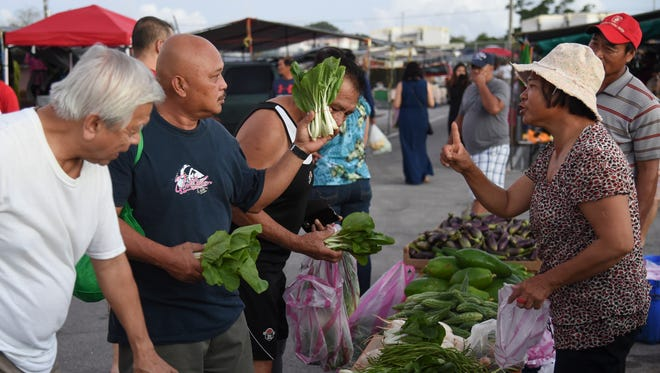 Albert Ignacio gets a one-dollar deal on bok choy at the grand opening of the Dededo flea market on Dec. 10, 2016.