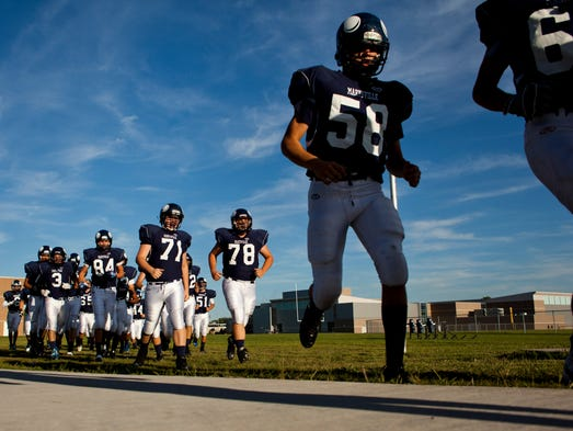 Marysville players file into the locker room before a football game August 28, 2014 at Marysville High School.