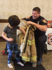 Sophia Phou tries on a firefighters coat with the help of Karl Brichford, a Canton firefighter/paramedic, on Saturday.