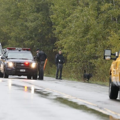 A K-9 unit searches a ditch on Hendy Hollow Road in