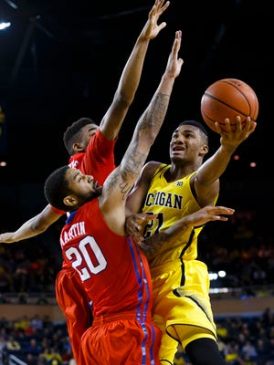 Dec 20, 2014;  Michigan Wolverines guard/forward Zak Irvin (21) goes to the basket on Southern Methodist Mustangs forward Justin Martin (20) and forward Ben Moore (00) in the first half at Crisler Center.