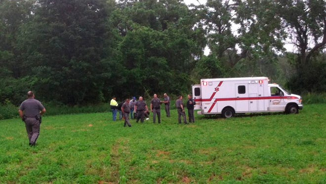Police gather around David Sweat after he was shot and captured near the Canadian border Sunday, June 28, 2015, in Constable, N.Y.