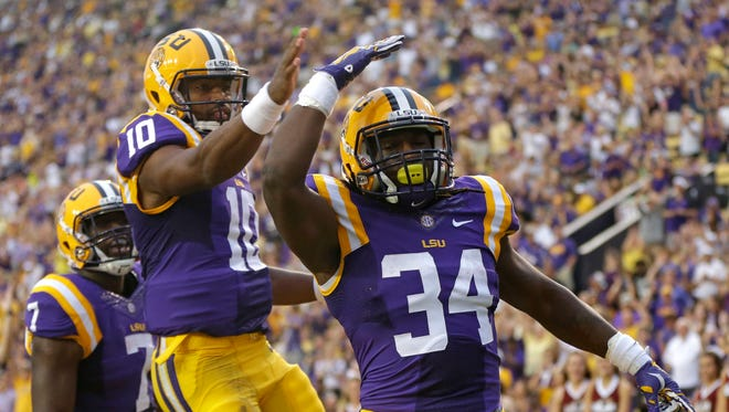 LSU running back Darrel Williams (34) celebrates his rushing touchdown with quarterback Anthony Jennings (10) and running back Leonard Fournette during the Tigers 31-0 win over Louisiana-Monroe on Saturday.