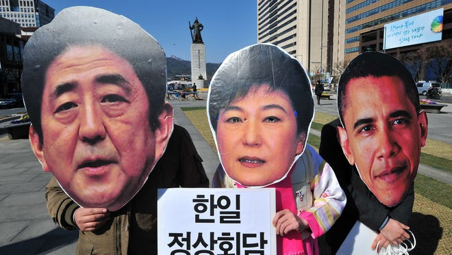 South Korean activists wear the masks of South Korean President Park Geun-Hye, Japanese Prime Minister Shinzo Abe, and President Obama.