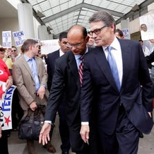 FILE - In an Aug. 19, 2014 file photo, Texas Gov. Rick Perry, front right, is escorted away from the Blackwell Thurman Criminal Justice Center, in Austin, Texas. Just when Perry was feeling like governor non grata, a felony indictment accusing him of abusing his power has energized Texas conservatives, who claim it's a politically motivated attack in an important election year. It's also put the spotlight back on Perry, who is trying to rehabilitate his political image before leaving office in January and convince would-be 2016 Republican primary voters across America he's worth a second look following an embarrassing White House bid three years ago.