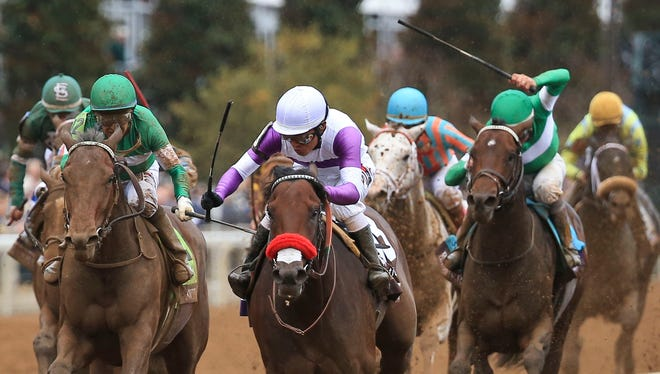 Mario Gutierrez aboard Nyquist fends off Victor Espinoza and Swipe near the finish line to win the Breeders' Cup Juvenile at Keeneland Saturday.