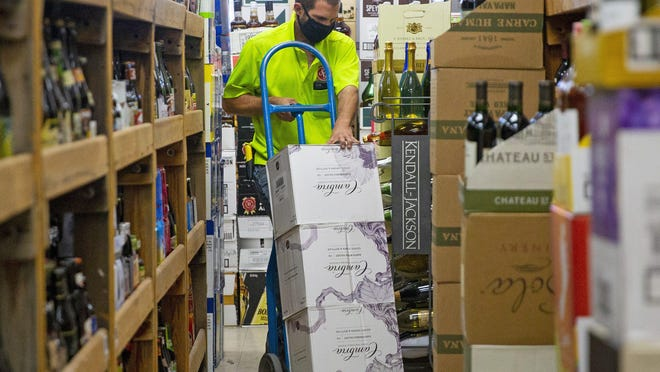 Nathan Gordon, with Southern Glazer's Wine and Spirits, stocks shelves at Tops Liquors in Tempe, Arizona, on April 2, 2020. Sales of at-home alcohol, according to a Nielsen report from June, have spiked nearly 27% since the start of the pandemic.