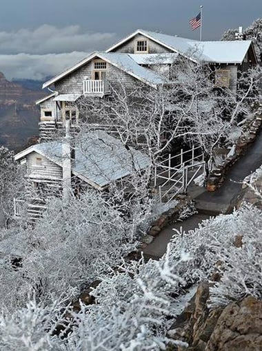 Trees, fences and the historic Kolb Studio building are frosted with snow and ice. Features within the canyon are grayed out. A blanket of clouds crosses on the far side of the abyss.