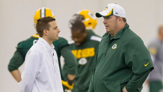Green Bay Packers head coach Mike McCarthy, right, and Eliot Wolf, director of pro personnel, watch during NFL football rookie camp Friday, May 16, 2014, in Green Bay, Wis.