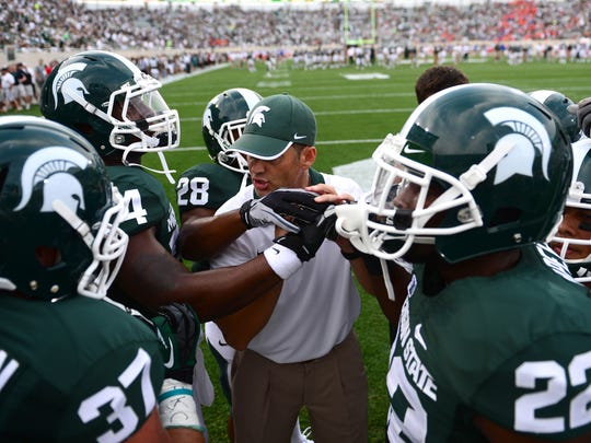 Aug 31, 2012; East Lansing, MI, USA; Michigan State Spartans running backs coach Brad Salem huddles prior to the game against the Boise State Broncos at Spartan Stadium.