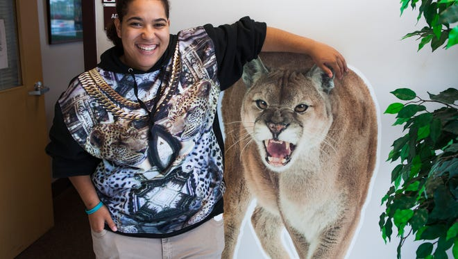 Kadedra Johnson, a senior at Stuarts Draft High School selected by teachers and guidance counselors as their outstanding student of the year, poses with a cutout photo of a cougar at the school on Tuesday, May 26, 2015.