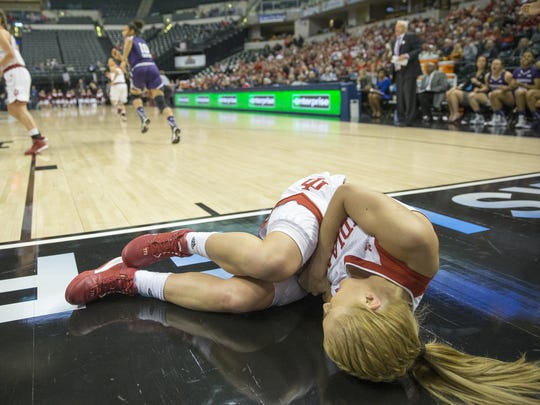 Tyra Buss lies off the baseline after landing hard on her left elbow during play against Northwestern, Big Ten Women's Basketball tournament, at Bankers Life Fieldhouse.