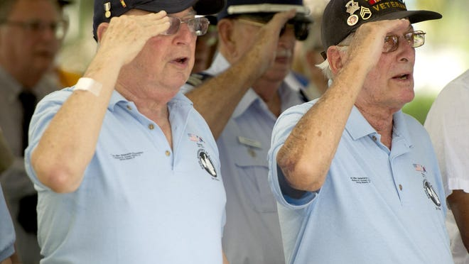 Army veteran Howard Garlin (left) participated in local veterans groups.  Here, with Shelly Evans, the Korean War veteran salutes at a 2017 service commemorating V-J Day, which ended World War II.