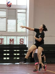 A member of the women's team goes for a spike during
