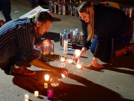 Dustin Cosby, left, an associate professor at Umpqua Community College, blows out candles following a vigil for the 10 dead and seven wounded in Thursday's attack at the Roseburg, Ore., community college. Helping him is Meriah Calvert, who said she knows three of the victims.