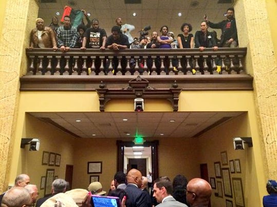 Protesters shout as council members leave the chamber at city hall in Baltimore.