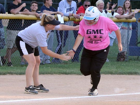 """GMC All-Star softball game held at Pitt Street Park in South Plainfield on Tuesday June 14, 2016.Pink Team senior # 20 Ashli Venokur of East Brunswick High School gets a """"high-five"""" from a coach as she round third base and heads home after hitting a three run home run in the first inning."""