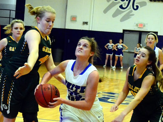 White House High junior Bailey Hutchison drives to the basket between Gallatin senior Keile Hale (left) and junior Katey Rogers during first-quarter action. Hutchinson scored two points.