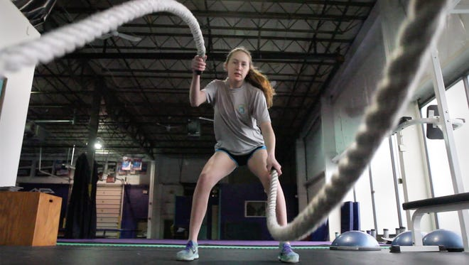 Rene Gangarosa works out using heavy ropes as she utilizes a variety of cross fit training exercises at Dynamic Elite in Gates Friday, March 25, 2016.