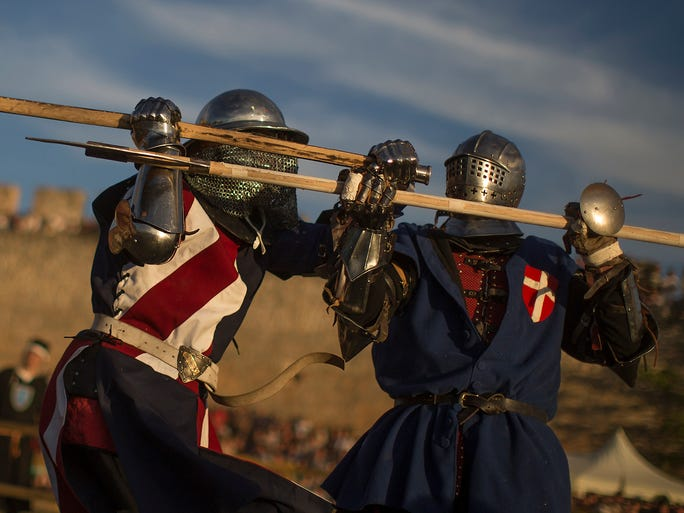 A pair of fighters from Denmark, right, and the U.S. left, compete during a Medieval Combat World Championship tournament in Belmonte, Spain, Thursday, May 1, 2014. The Championship recreates the medieval culture and it takes place from May 1 till May 4 in the Castle of Belmonte. (AP Photo/Andres Kudacki) ORG XMIT: AK103