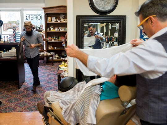 Hazel Vazquez, left, walks through the shop as friend and co-owner Tony Bordonaro, right, gives customer Derek Byers a hot shave Tuesday, Jan. 24, 2017, in Naples. The two opened up the old-school shop after meeting at the Bonita School of Cosmetology.