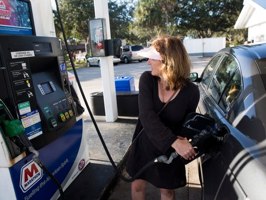 Angie Pugliese pumps gas at the Marathon gas station on the corner of Davis and Collier Boulevard.