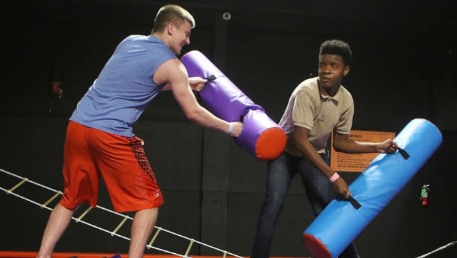 Nathlee Strickland, 18, plays a fighting game with Nick Reese, 14, at Altitude Trampoline Park in Monroe, La. on Thursday, March 31, 2016. The game ended when Strickland, left, pushed Reese off the balance beam and into a pit filled with foam blocks below.