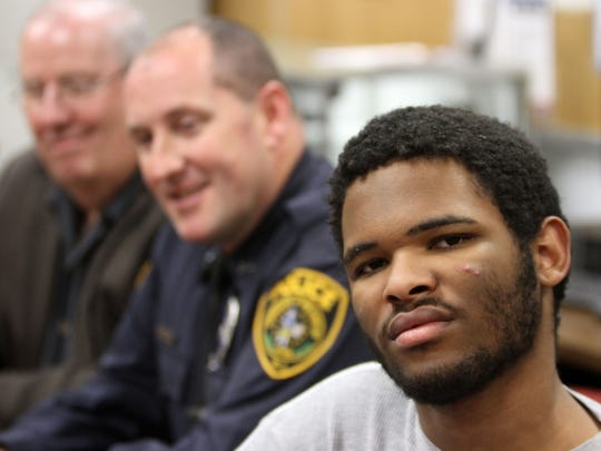 Zion Miller, 16, who is autistic and nonverbal, plays on a tablet, which was a gift from Franklin Township Police Officer Richard Hartnett (center) and donated by Jim O'Neil (left) of Electronics Enterprise in Somerset, during a press conference about the gift at Franklin Township Police Department in Somerset on Thursday, Dec. 3, 2015.