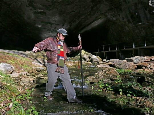 Smallin Civil War Cave staff archeologist Eric Fuller crosses a small stream flowing out of the cave.