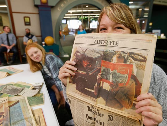 Ashley Birtciel holds up a newspaper clipping of her