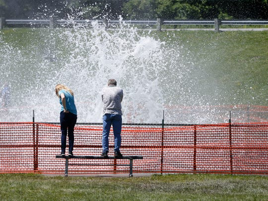 Marilyn and Marty Mauk of Des Moines look on as water splashes up over the railing Monday, July 2, 2018, at the Saylorville Lake spillway in Johnston.