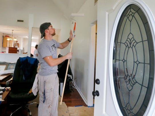 Nicholas King paints the living room walls of veteran