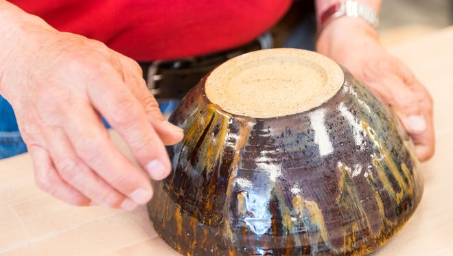 Roy Kaneshiki shows off a completed bowl at Clay College in Millville on Wednesday, May 17.