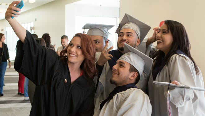 Las Montañas Charter High School's english teacher Amber Emeterio takes a selfie with a group of graduates.