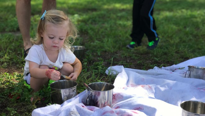 A child experiments with making dye using frozen berries.