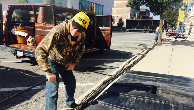 Dick Eckard volunteered during the set up of the Popcorn Festival on Wednesday by installing electrical cables.