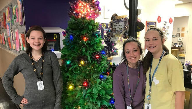 Ashlynn Jenkins, left, an eighth-grade student at Wylie Junior High School, poses with seventh-grade students Audree Leicht and Brylee Pursley at their school's new Christmas tree. The tree, made of plastic bottles cut to shape and decorated by plastic cutouts made by the students and others in Hollie Garza's Art I classes, will be auctioned off to the highest bidder next week.