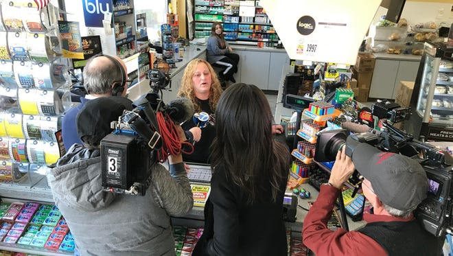 An attendant speaks to reporters after the NJ Lottery announced the winning Mega Millions ticket, worth $521 million, was sold at the Lukoil station on Route 23 south in Riverdale, N.J.